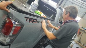 man putting paint protection film on a truck
